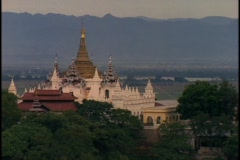 A beautiful, ancient Buddhist temple stands in front of a mountain range in - stock footage