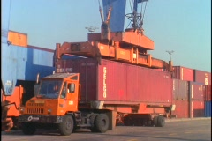 A crane unloads a shipping container from a truck. Stock Footage