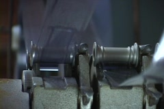 Hands control film as it feed through a roller. Stock Footage