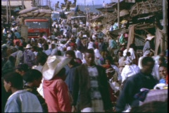A market in Africa swarms with crowds of shoppers and vendors. - stock footage