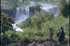 An Ethiopian tribe walks in front of the Blue Nile waterfall. - stock footage