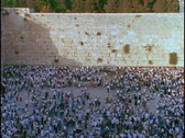 Stock Video Footage of A crowd of people mills about at the Wailing Wall in Israel.