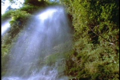 A beautiful tropical waterfall cascades down a cliff. Stock Footage