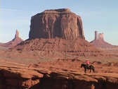 A cowboy on horseback rides through in Monument Valley, Utah. Stock Footage