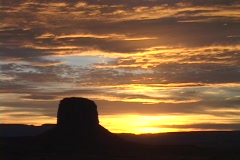 A butte stands in silhouette beneath golden clouds in Monument Valley. Stock Footage