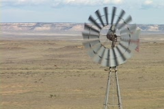 A windmill spins in the desert Stock Footage