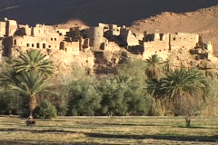 A Moroccan man rides a donkey past a desert fortress. Stock Footage