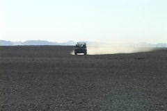 A Range Rover Land Cruiser speeds across a desert throwing up dust. Stock Footage