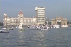 Boats enter and exit the harbor with the Taj Mahal Hotel in the background in Stock Footage