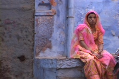 A woman sits in colorful clothing in a blue alley way in Jodhpur, India. Stock Footage