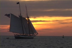 Large sailboat or clipper ship, sails toward the horizon during golden hour. Stock Footage