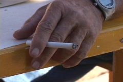 An old man's hand holds a burning cigarette. Stock Footage