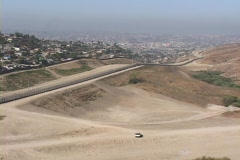 A border-patrol vehicle sits beneath the fence in the U.S. , Mexico border Stock Footage