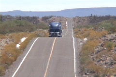 A semi truck traverses a hilly desert road. - stock footage