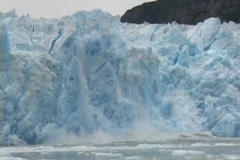 A blue wall of ice falls off an iceberg. - stock footage