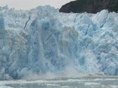Stock Video Footage of A blue wall of ice falls off an iceberg.