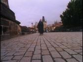 A peasant woman in Czech Slovak republic crosses a bridge in Prague. Stock Footage