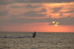 A windsurfer cuts across the water in silhouette against an orange sun. Stock Footage