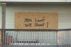 Medium shot of a boarded up house warning  looters not to enter after Hurricane Stock Footage