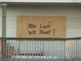 Stock Video Footage of Medium shot of a boarded up house warning  looters not to enter after Hurricane