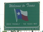 Stock Video Footage of A sign welcomes visitors to Texas, home of George W. Bush.