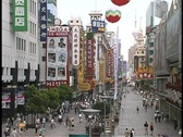 Businesses and pedestrians fill a shopping district in Shanghai, China. Stock Footage