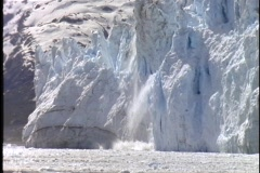Stock Video Footage of A large chunk of an Alaskan glacier falls into the sea.