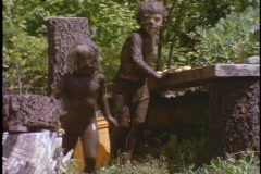 Children, covered in mud, slide into a muddy hole. Stock Footage