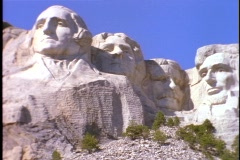 The massive, carved images of four American presidents rise against a blue sky Stock Footage