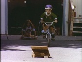 Stock Video Footage of Children ride and jump ramps on bicycles and toy vehicles.