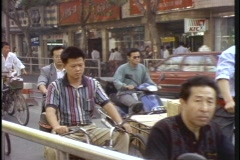 Crowds of bicyclists ride down a street in China. Stock Footage