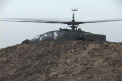 An Apache helicopter lifts off from rough terrain. Stock Footage