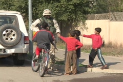 U.S. soldier talks to children on the street in Iraq. Stock Footage