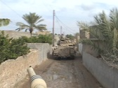 Stock Video Footage of Abrams tanks move through an Iraq village.