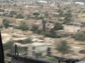Stock Video Footage of A Black hawk helicopter carrying soldiers flies over Baghdad.