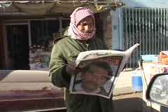 An Iraqi man reads a newspaper with a picture of Saddam Hussein on the cover. Stock Footage