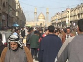 Stock Video Footage of Iraqis walk and shop in a busy outdoor market of Baghdad, Iraq.