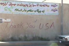 Cars and pedestrians pass by a  thank you sign to the U.S.A. on a wall in Stock Footage