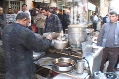 An Iraqi street vendor serves hot tea as other Iraqi men watch. Stock Footage