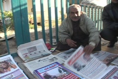 An Iraqi vendor shows a newspaper with headlines of Saddam Hussein's capture. Stock Footage