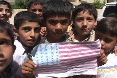 An Iraqi boy holds up a drawing of the American flag in Baghdad. Stock Footage