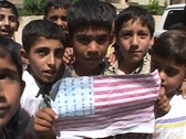Stock Video Footage of An Iraqi boy holds up a drawing of the American flag in Baghdad.