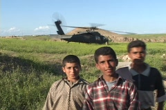 Iraqi boys pose and give peace signs in front of a Blackhawk helicopter. Stock Footage