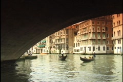 Tourists ride gondolas under the Rialto Bridge on the Grand Canal in Venice, Stock Footage