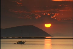 A fishing boat rests in calm waters as birds fly over the golden-hour sun in a Stock Footage