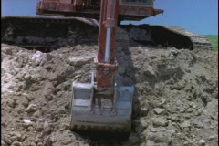 A steam shovel scoops and dumps dirt at a construction site. Stock Footage