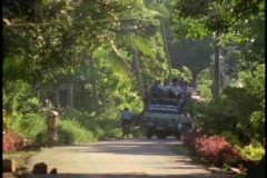 Natives ride on the top of a crowded mini bus down a street in Indonesia. Stock Footage