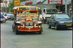 A jeepney drives down a street in Manila, Philippines. Stock Footage