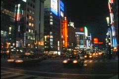 Heavy traffic drives below bright neon lights in Tokyo, Japan. Stock Footage
