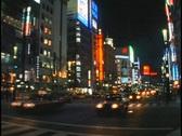 Stock Video Footage of Heavy traffic drives below bright neon lights in Tokyo, Japan.